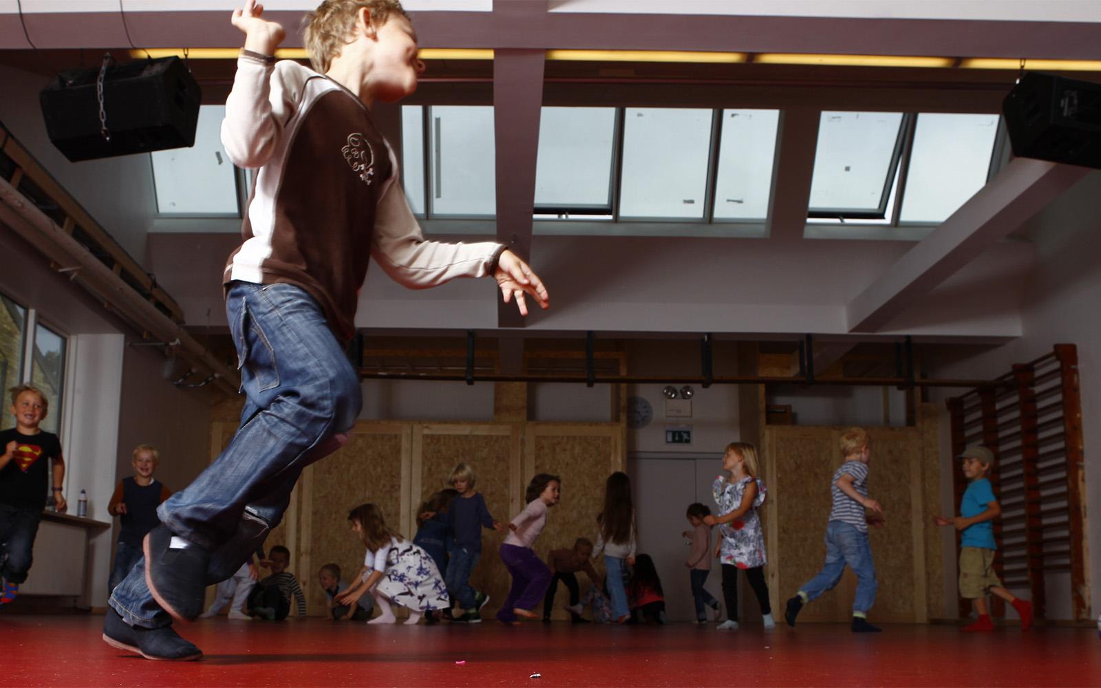 Schüler spielen in der Schulturnhalle die mit Dachverglasung und Dachbelüftung eingerichtet ist