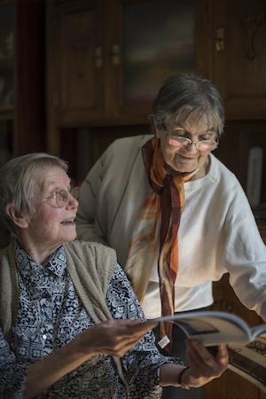 Zwei gesunde ältere Damen, die über eine Zeitschrift sich besprechen